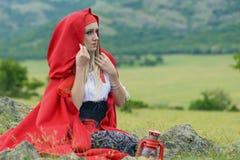 Красивая белокурая женщина в старомодном платье и красном плаще сидя на луге Стоковое Изображение