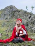 Красивая белокурая женщина в старомодном платье и красном плаще Стоковые Изображения RF