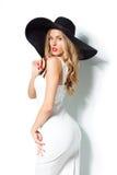 Красивая белокурая женщина в черной шляпе и белом элегантном платье вечера представляя на изолированной предпосылке фасонируйте в Стоковая Фотография