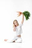 Красивая белокурая женщина держа свежую морковь с зеленым цветом выходит на белую предпосылку здоровье диетпитания стоковые изображения rf
