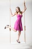 Красивая белокурая женщина на качании против белизны Стоковые Изображения RF