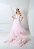 Красивая белокурая женщина нося шикарное длинное платье и кристалл увенчивают представлять в студии на белой полигональной предпо Стоковое Фото
