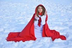 Красивая белокурая женщина представляя в снеге стоковое изображение
