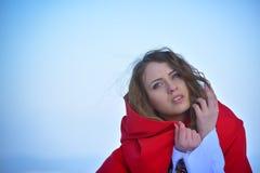 Красивая белокурая женщина представляя в снеге стоковое фото