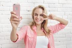 Красивая белокурая женщина принимая фото с камерой мобильного телефона Стоковое Изображение RF