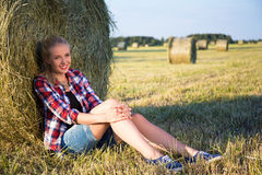 Красивая белокурая женщина сидя около стога сена в поле Стоковые Изображения