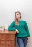 Красивая белокурая женщина стоя около комода ящиков Стоковое Фото
