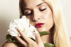 Красивая белокурая женщина с белым цветком и губами rep Стоковая Фотография