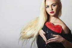 Красивая белокурая женщина с красным сердцем. Девушка красоты. Покажите символ влюбленности. День валентинок стоковое фото rf