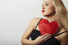 Красивая белокурая женщина с красным сердцем. Девушка красоты. Покажите символ влюбленности. Day.Passion валентинки Стоковые Изображения RF