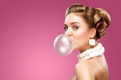 Красивая белокурая женщина дуя розовая жевательная резинка портрет способа стоковое фото