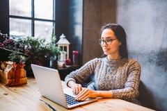 Красивая бизнес-леди бизнес-леди брюнет использует компьтер-книжку, шкалы, печати отправляет СМС на клавиатуре В кофейне, сидя на Стоковые Фотографии RF