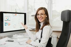 Красивая бизнес-леди в деятельности костюма и стекел на компьютере с документами в светлом офисе стоковое фото