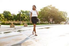 Красивая бизнес-леди идя outdoors говорить мобильным телефоном стоковое изображение