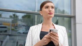 Красивая бизнес-леди используя телефон около офиса outdoors сток-видео