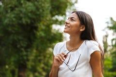 Красивая бизнес-леди сидя в парке outdoors представляя стоковое фото