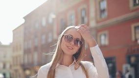 Красивая бизнес-леди с солнечными очками идет через город пешком Смотреть на окраинах города Лето акции видеоматериалы