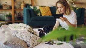 Красивая блондинка красит губы кладя на состав используя профессиональные декоративные косметики сидя на кровати дома сток-видео