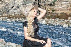 Красивая блондинка молодой женщины с длинными волосами в шляпе сидя на скалистом береге рекой Вокруг гор стоковая фотография