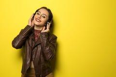 Красивая бразильская девушка наслаждаясь музыкой с головой знонит по телефону внутри Стоковое фото RF