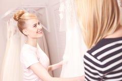 Красивая будущая невеста покупает белую мантию Стоковое Изображение