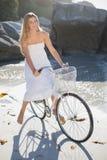 Красивая блондинка в белых sundress на езде велосипеда на пляже Стоковые Фотографии RF
