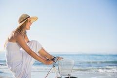 Красивая блондинка в белых sundress на езде велосипеда на пляже Стоковая Фотография RF