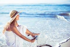 Красивая блондинка в белых sundress на езде велосипеда на пляже Стоковое фото RF
