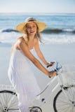 Красивая блондинка в белых sundress на езде велосипеда на пляже Стоковые Фото