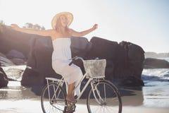 Красивая блондинка в белых sundress на езде велосипеда на пляже Стоковое Фото