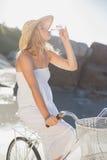 Красивая блондинка в белых sundress на питьевой воде велосипеда на пляже Стоковые Изображения