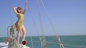Красивая блондинка в золотом платье стоит на краю яхты snaking на море в солнечном дне и держать акции видеоматериалы