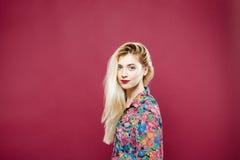 Красивая блондинка в красочной рубашке смотря камеру и усмехаясь на розовой предпосылке Милая девушка представляет в студии Стоковое Изображение RF