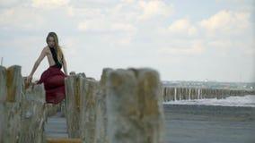 Красивая блондинка в платье держит на деревянные столбы и виды в воздухе в середине лимана между видеоматериал
