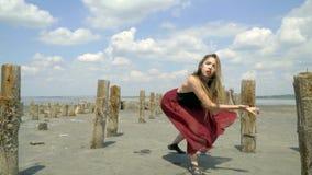 Красивая блондинка в платье пахнуть в грязи необычно танцует вдоль лимана между покинутыми бассейнами соли видеоматериал
