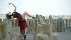 Красивая блондинка в платье установила ее ногу в грязи на деревянных столбах в середине лимана между покинутым солью сток-видео
