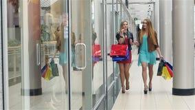 Красивая блондинка идет вдоль окон магазина, обсуждая видеоматериал