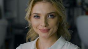 Красивая блондинка при состав и стиль причёсок, шаловливо усмехаясь на камере ногти красотки nailfile полируя салон видеоматериал
