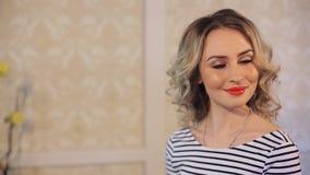 Красивая блондинка смотрит камеру, красные губы и яркий состав видеоматериал