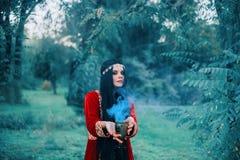 Красивая ведьма подготавливала напиток любов Чашка производит волшебный голубой дым Женщина пробует заколдовывать востоковедно стоковые фотографии rf