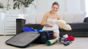 Красивая вещь s упаковки молодой женщины на летний отпуск в чемодане акции видеоматериалы