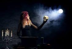Красивая ведьма делая колдовство на закоптелой предпосылке Изображение хеллоуина Стоковое фото RF