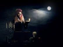 Красивая ведьма делая колдовство на закоптелой предпосылке Изображение хеллоуина Стоковое Фото