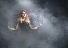 Красивая ведьма делая колдовство над закоптелой предпосылкой Стоковое Изображение