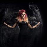 Красивая ведьма делая колдовство над закоптелой предпосылкой Стоковые Изображения