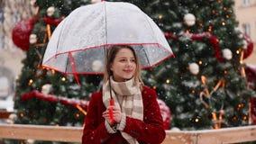 Красивая взрослая девушка в красных пальто и шарфе с зонтиком сток-видео