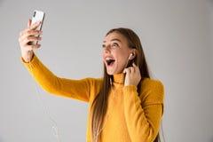 Красивая возбужденная счастливая молодая женщина над серой предпосылкой стены используя говорить мобильного телефона стоковая фотография rf