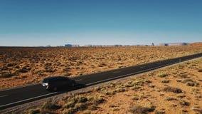 Красивая воздушная съемка вождения автомобиля минифургона вдоль изумительной американской дороги шоссе пустыни, плоских гор на го сток-видео