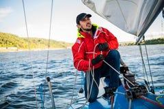 Красивая воодушевляя съемка приключения действия матроса или капитана на яхте или паруснике прикрепляя большой mainsail или стоковые изображения rf