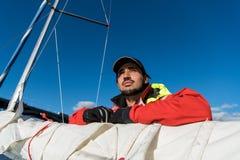 Красивая воодушевляя съемка приключения действия матроса или капитана на яхте или паруснике прикрепляя большой mainsail или стоковые фото